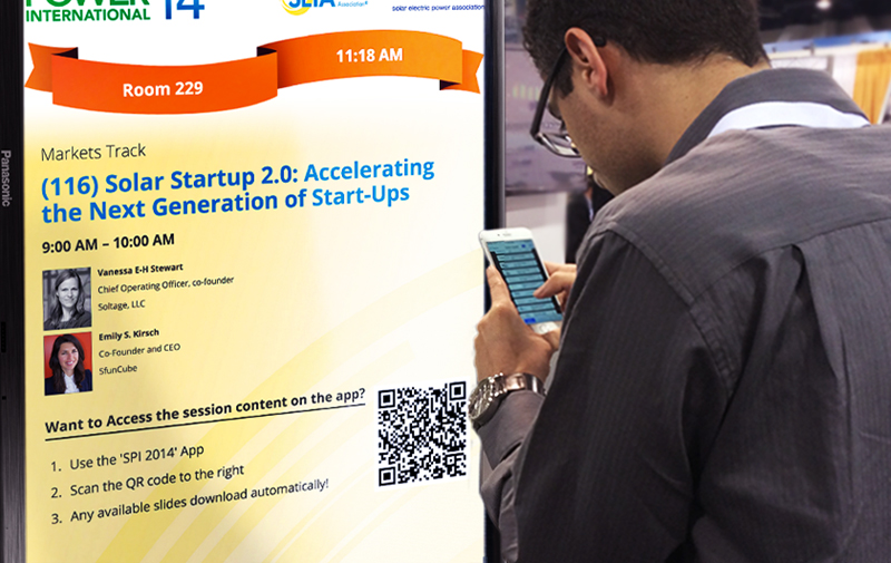 A conference attendee scans a QR code on a digital display that's being used as digital signage with his event app.