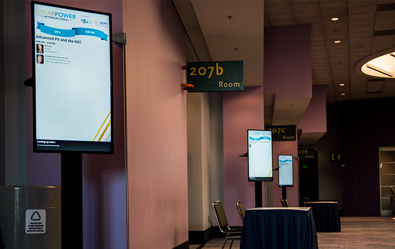 Digital room signage features presentation information, speaker headshots and biographies, and a section that alerts attendees about upcoming sessions at your conference.